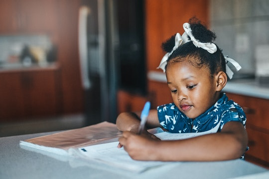 little girl writing in notebook at the kitchen table