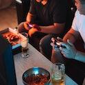 Guys playing video games holding joysticks.