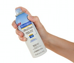 Chillicothe, Ohio, USA - July 5th, 2011: Woman\'s hand holding Neutrogena Ultra Sheer Body Mist Sunb...
