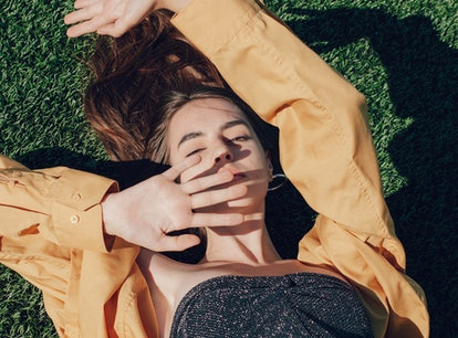 Young woman laying in the grass while reading her new moon in Leo horoscope.