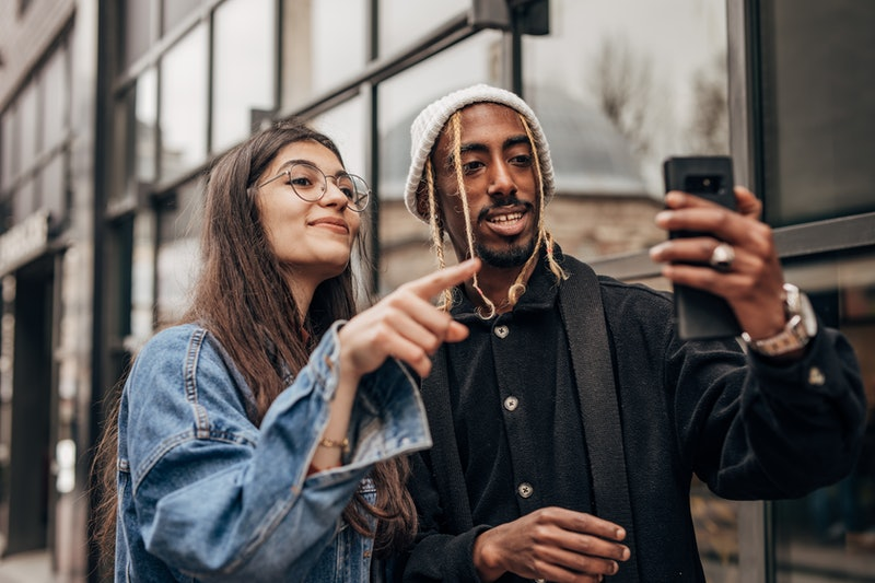 A man and a woman search for filters on TikTok and try them on using iPhone.