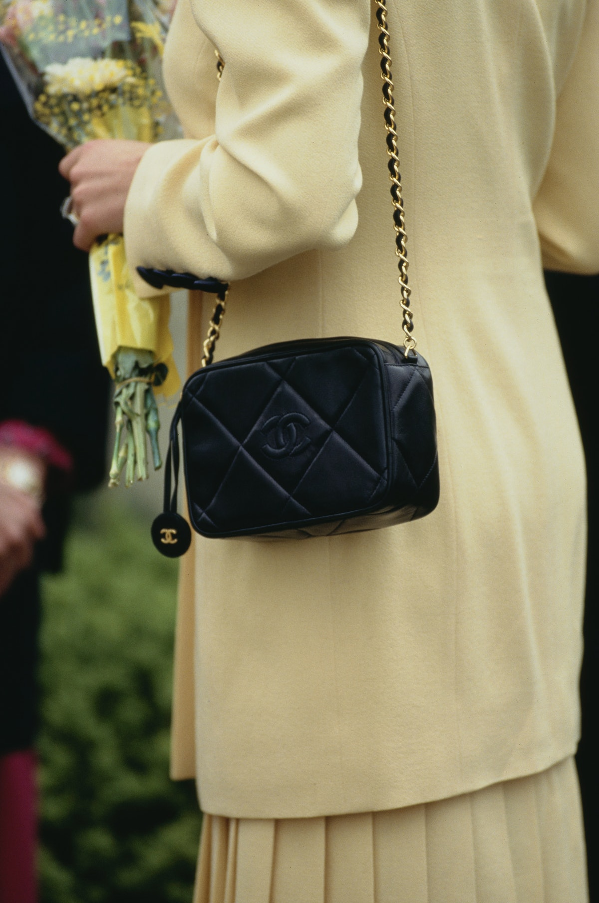 Diana, Princess of Wales wearing a yellow skirt suit and a Chanel quilted bag