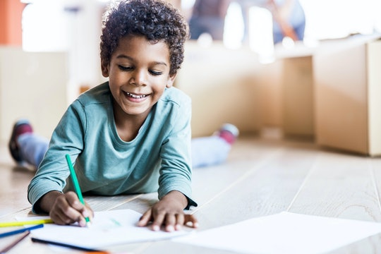Small boy smiling while drawing on the floor