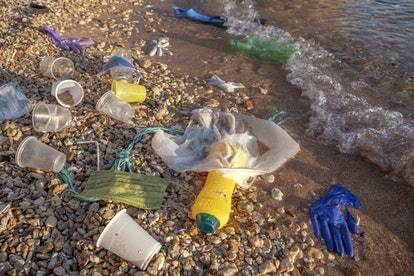 RED SEA, SHARM EL SHEIKH, EGYPT - OCTOBER 2020: Plastic debris and face masks on the beach in surf z...