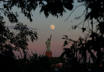 JERSEY CITY, NJ - JUNE 23: An almost full moon rises above the Statue of Liberty as the sun sets in ...