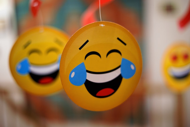 Close-up of handing round paper emoticon. Yellow laughing face with big blue tears at eyes. Selectiv...