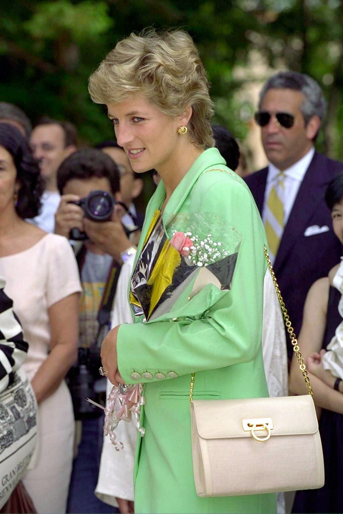 Princess Diana, Princess Of Wales at the Venice Biennale wearing a pastel green blazer and cream Salvatore Ferragamo bag. She has been given flowers by a fan.