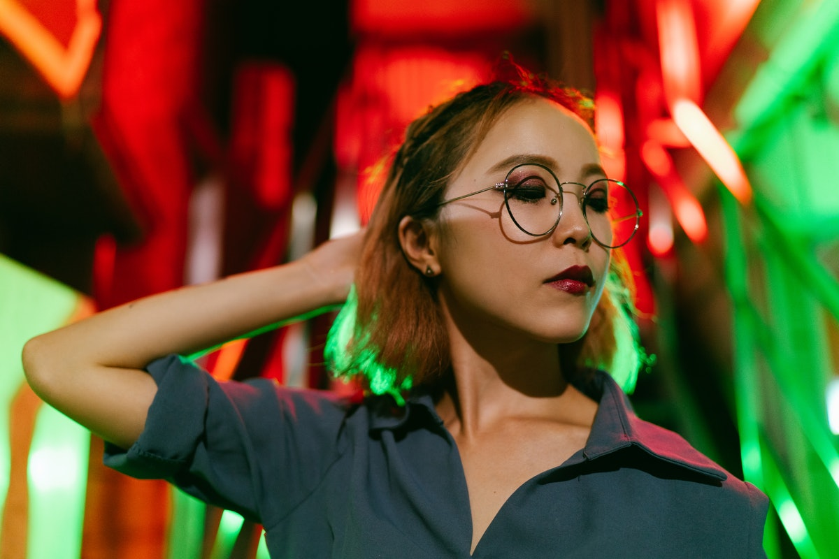 A portrait of a young woman lit up by neon lights the night of Friday the 13th 2021.