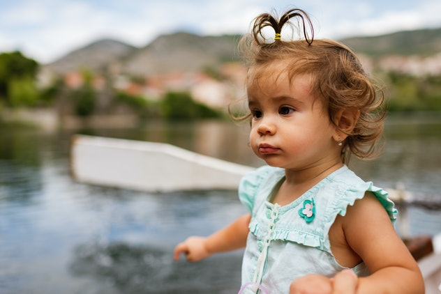 Young happy baby girl enjoying boat ride on a river.