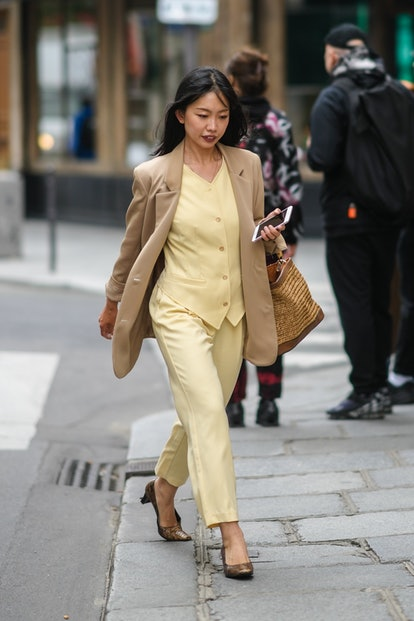 PARIS, FRANCE - JUNE 23: A guest wears a beige oversized blazer jacket, a pale pastel yellow double breasted top, suit pastel yellow cropped pants, brown pointed snake print shoes, a brown wicker bag, outside BLUEMARBLE, during Paris Fashion Week - Menswear Spring/Summer 2022, on June 23, 2021 in Paris, France. (Photo by Edward Berthelot/Getty Images)