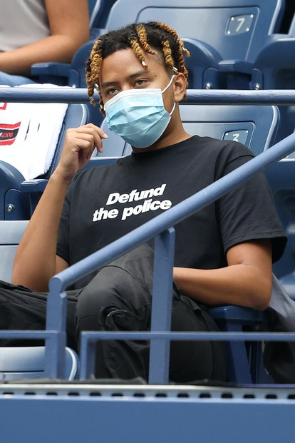 """Cordae wears a """"defund the police"""" shirt while watching as Naomi Osaka at the 2020 US Open."""