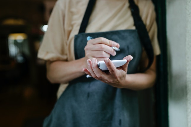 A waitress standing in the doorway of a restaurant and writing on her notepad.