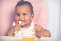 Cute baby child eating pureed mango with a teaspoon.