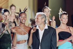 Italian fashio, designer Gianni Versace, with models, British Naomi Campbell and Canadian Linda Evangelista, acknowledges the audience at the end of the presentation of the Fall/Winter Haute Couture collections in Paris on July 6, 1996. (Photo by Thomas COEX / AFP)        (Photo credit should read THOMAS COEX/AFP via Getty Images)