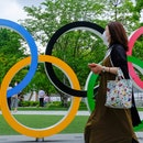 TOKYO, JAPAN - 2021/07/15: A woman wearing a face mask walks past Olympic Rings near the National St...