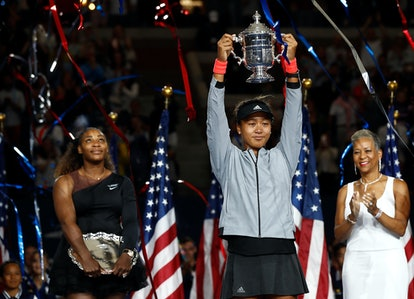 Naomi Osaka poses with the championship trophy at the 2018 US Open.