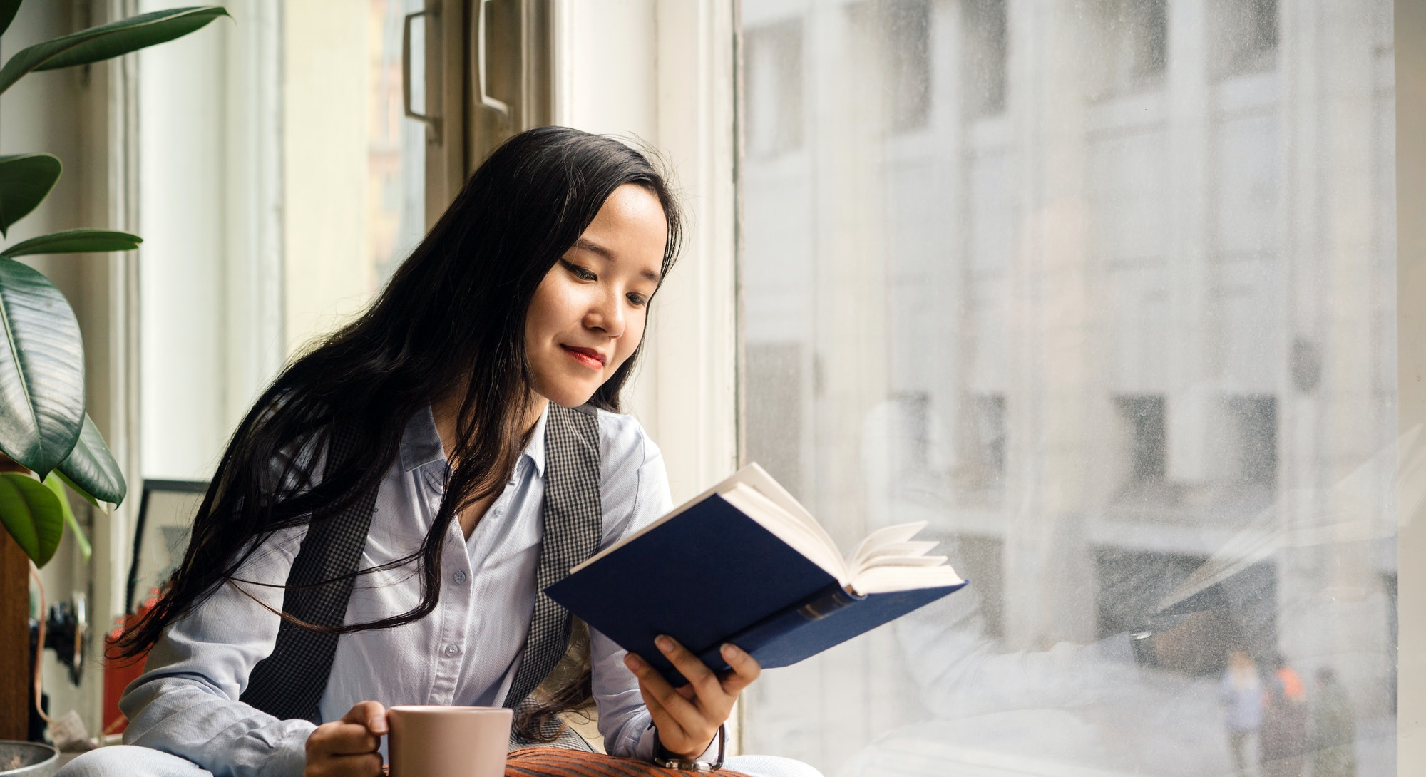 Young asian woman sitting by the window on the sofa with a cup of tea, book and pillow, laughing. Remote work at home. Mental health and relax