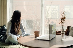 Young asian woman sitting by the window on the sofa with a laptop on a pillow in lotus position and ...