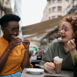 Two friends laughing while drinking coffee together after reconnecting. Experts explain how to reconnect with an old friend after losing touch.