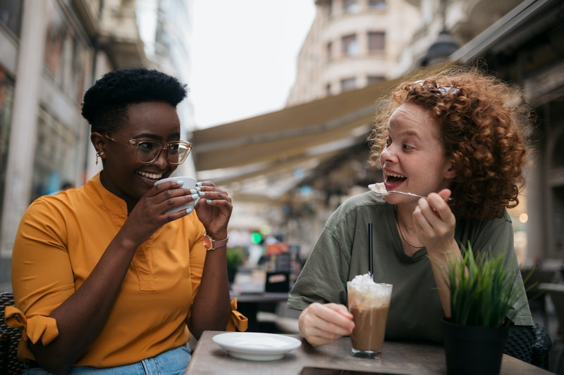Two friends laughing while drinking coffee together after reconnecting. Experts explain how to recon...