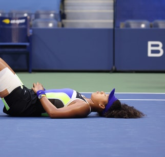 NEW YORK, NEW YORK - SEPTEMBER 12: Naomi Osaka of Japan lays down in celebration after winning her W...