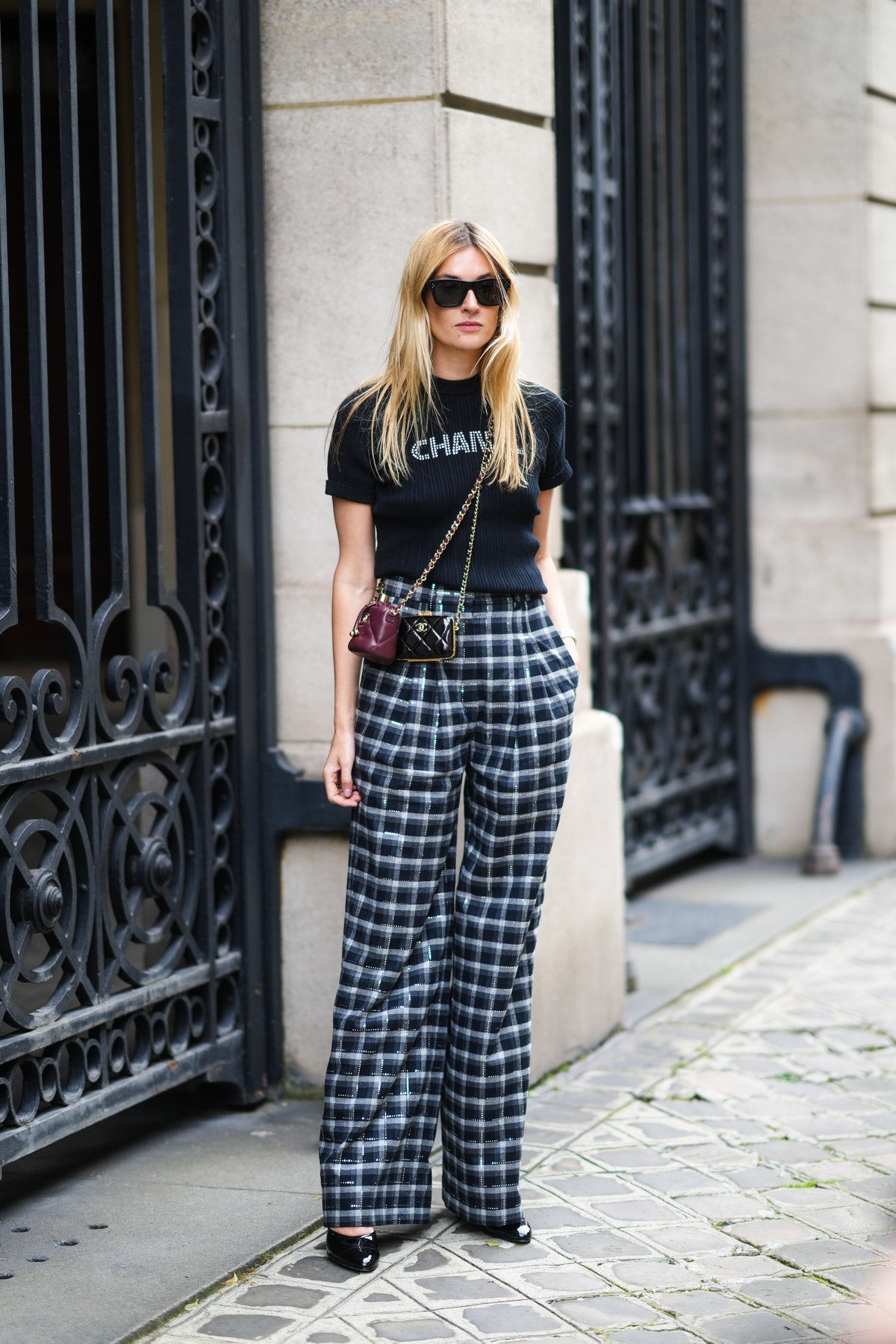 Camille Charriere wears a black ribbed with white Chanel rhinestones logo crop-top from Chanel, blac...