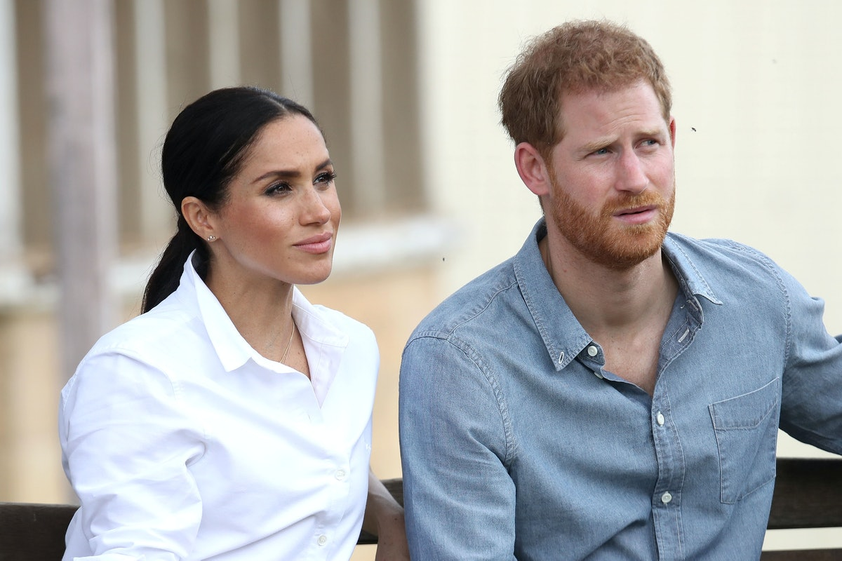 """Harry and Meghan are pictured here sitting on a bench, and William and Charles are reportedly """"nervous"""" about Harry's new memoir."""