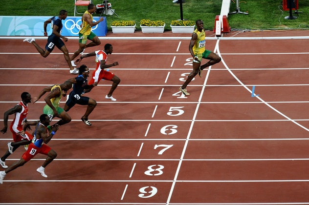 Jamaica's Usain Bolt (R) crosses the finish line to win the men's 100m final at the National Stadium...