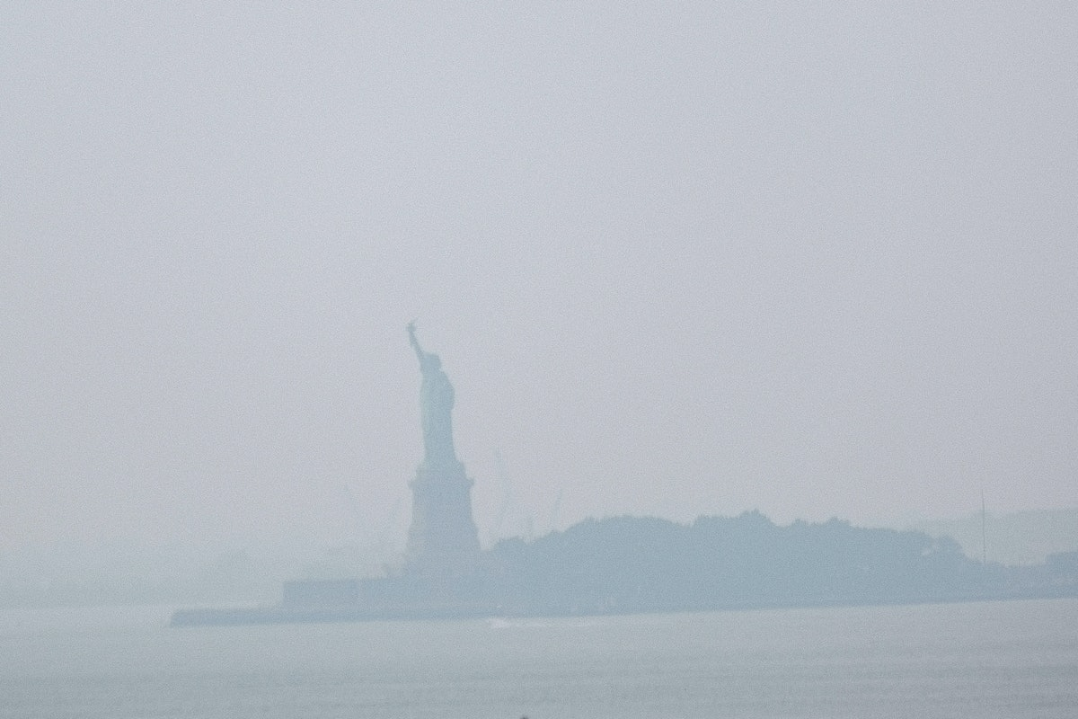 NEW YORK, NEW YORK - JULY 20: The Statue of Liberty sits behind a cloud of haze on July 20, 2021 in ...