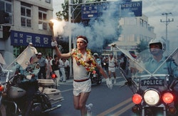 Lawrence Mac Donald holds the olympic flame in the streets of Seoul on August 30, 1988. (Photo by - ...