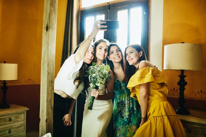Friends take a selfie at their coworker's wedding to post on Instagram with some wedding captions fo...