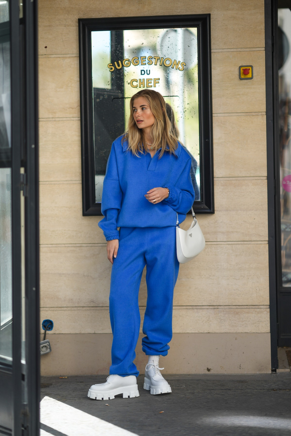 Xenia Adonts wears a pearls necklace, a royal blue V-neck sweater with matching large Shabderb jogge...