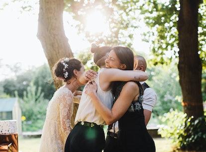 Young woman attending her coworker's wedding, hugging bride.