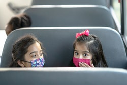 two little girls with face masks on a school bus