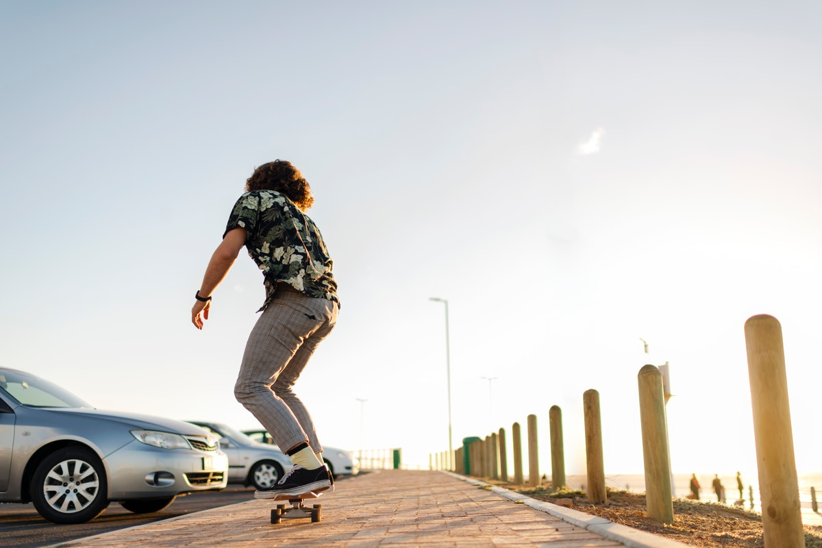 Back view young man with long hair skateboarding in car park