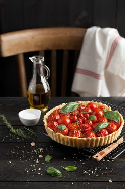 Cherry tomato tart with fresh basil leaves and thyme served on a cooling rack. A black wood plank wa...