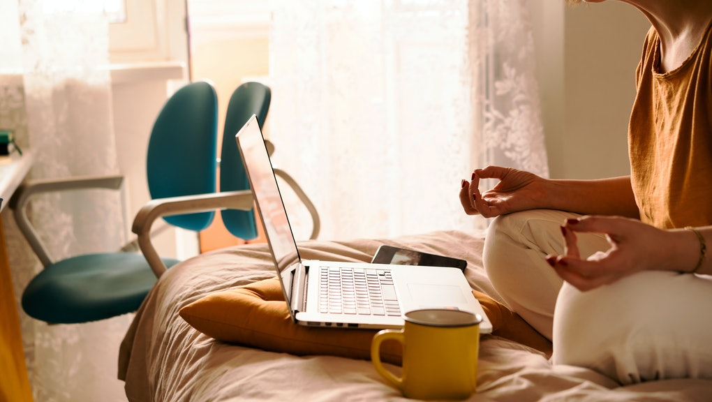A middle-aged woman in white jeans and a yellow sweater sitting on the bed in a yoga pose in front o...