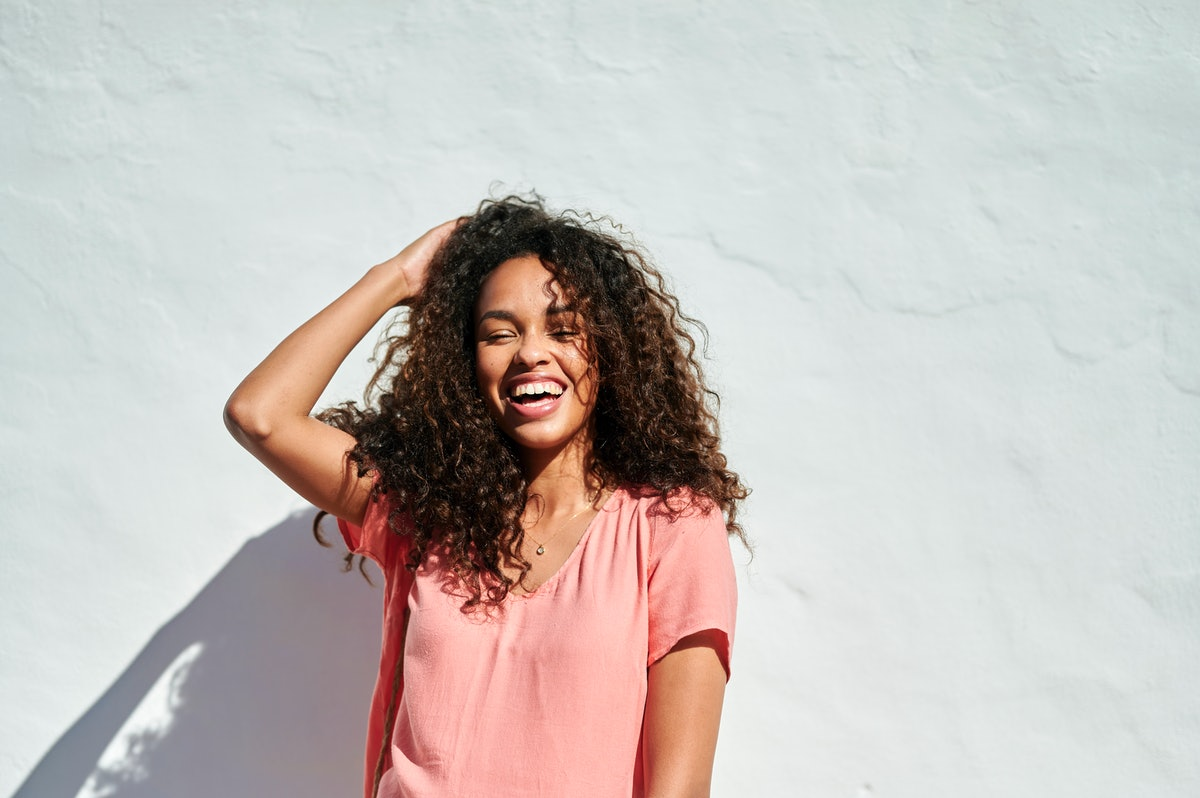 Smiling young woman with curly hair in sunlight, laughing the week of August 2, 2021, which will be ...