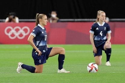 TOPSHOT - Britain's forward Georgia Stanway (L) and Britain's midfielder Keira Walsh take a knee before the Tokyo 2020 Olympic Games women's group E first round football match between Great Britain and Chile at the Sapporo Dome in Sapporo on July 21, 2021. (Photo by ASANO IKKO and - / AFP) (Photo by ASANO IKKO/AFP via Getty Images)