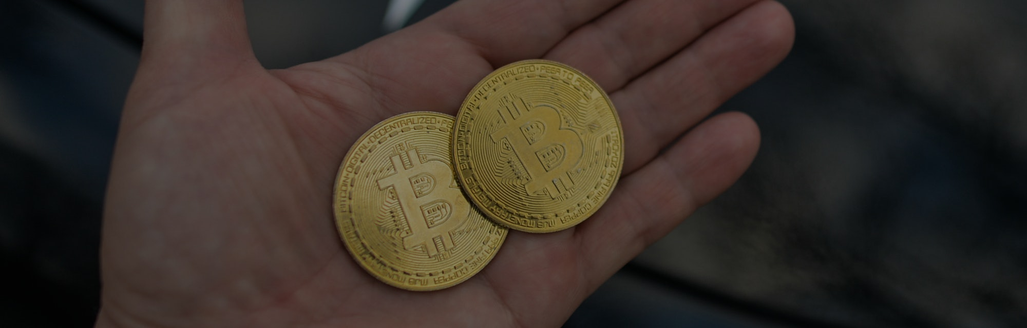 Illustrative image of two commemorative bitcoins seen in front of the Tesla car logo. On Saturday, F...