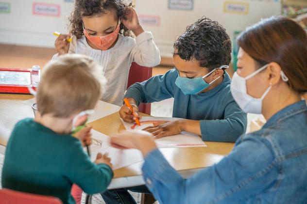 teacher and preschool students in class wearing face masks