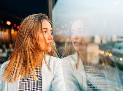 Charming thoughtful female in stylish wear leaning on hand and looking away in roof cafe at sunset