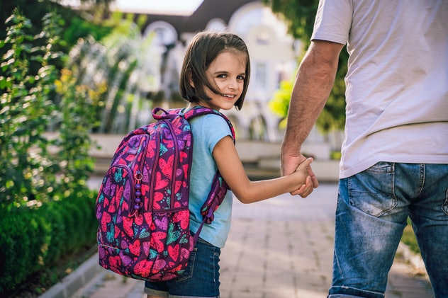little girl wearing a backpack on first day of school