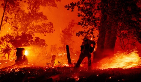 A firefighter works the line as flames push towards homes during the Creek fire in the Cascadel Wood...