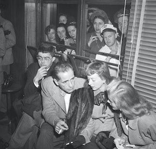 (Original Caption) 10/27/47-Washington, D.C.: Curious spectators peer through windows for a glimpse ...