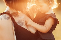 a tattooed mom holding her toddler outside in the sunshine