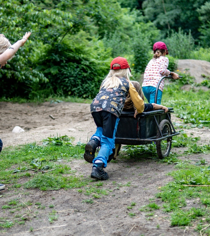 Children from the Wühlmäuse daycare center play with a trailer in the forest