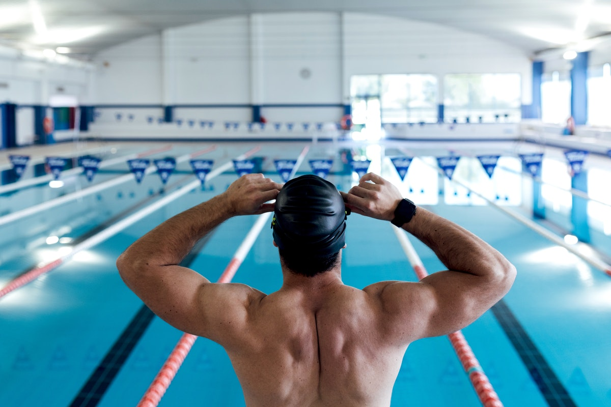 From above back view of anonymous strong male swimmer with naked torso sitting on starting platform ...