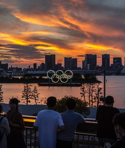 TOKYO, JAPAN - JULY 21: People gather to look at Olympic rings at sunset on July 21, 2021 in Tokyo, Japan. With the Olympics now just a few days away, Tokyo is bracing itself for a Games without foreign fans or local attendance and a population enduring its fourth state of emergency amid the continuing global coronavirus pandemic. (Photo by Yuichi Yamazaki/Getty Images)