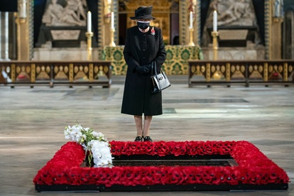 Queen Elizabeth II inspects a bouquet of flowers placed on her behalf at the grave of the Unknown Wa...